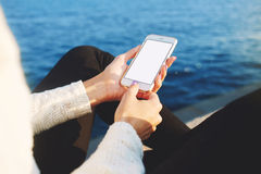 female chatting on-line on cell telephone while sitting on pier near sea Stock Photography