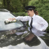 Female chauffeur cleaning windscreen of car Stock Photo