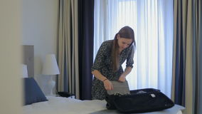 Female check weather outside and packing a suitcase in hotel stock video