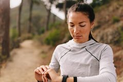 Female checking fitness progress on her smart watch. Female runner using fitness app to monitor workout performance, while standing outdoors on country road Stock Photo