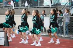 High school football cheerleaders. Female cheerleaders performing routine at high school football game stock photo