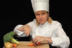 Female chef. A female chef cutting vegetables, black background stock image