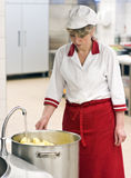 Female chef. A female chef filling out a large cauldron of potatoes with water to boil. Industrial kitchen interior stock photo