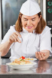 Female Chef Adding Spices To Dish. Mature female chef adding spices to dish at commercial kitchen counter Stock Image