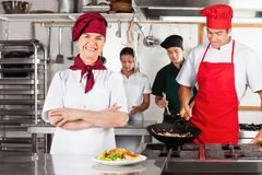 Female Chef With Arms Crossed In Kitchen Royalty Free Stock Images