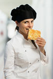 Female chef  biting a focaccia slice Royalty Free Stock Photos