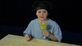 A female chef on a black background tastes a fruit smoothie and shows the `class` sign. A female chef on a black background tastes a fruit smoothie and shows the stock video footage