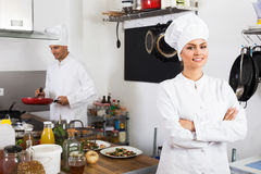 Female chef at cafe`s kitchen. Portrait of smiling young women in chef `s uniforme standing at cafe`s kitchen royalty free stock photography