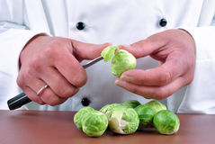 Female chef cleans Brussels sprouts Stock Photo