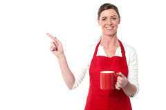 Female chef with coffee mug pointing away Stock Photography