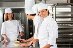 Female Chef With Colleagues In Commercial Kitchen Stock Photography