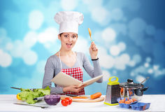 Female chef with the cookbook and a wooden spoon on blue background. Portrait of a woman in chef's hat reading cookbook and raising up a spoon, with blue boke Stock Photo