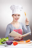 Female chef with the cookbook and a wooden spoon on gray background Royalty Free Stock Photography
