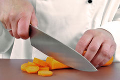 Female chef cuts a carrot Stock Photo