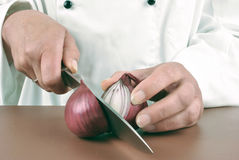 Female chef cuts an lilac onion Stock Photo