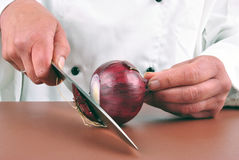 Female chef cuts an lilac onion Royalty Free Stock Photos