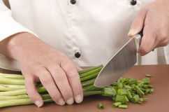 Female chef cuts spring onion with a large knife Royalty Free Stock Photos