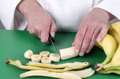 Female chef cutting a banana Royalty Free Stock Image