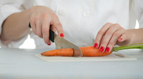 Female chef cutting carrots Stock Photos