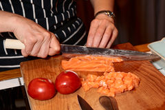 Female chef is cutting salmon Royalty Free Stock Photos