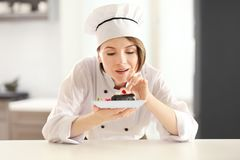 Female chef decorating tasty dessert. In kitchen stock images