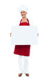Female chef displaying blank white ad board Royalty Free Stock Image
