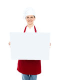 Female chef displaying blank white ad board Stock Photos