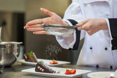 Female chef finishing a dessert plate Stock Photo
