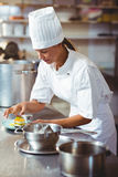 Female chef finishing dessert plates. In commercial kitchen Stock Images