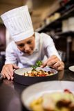 Female chef garnishing delicious desserts in a plate. At hotel stock images