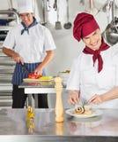 Female Chef Garnishing Dish In Kitchen. Happy female chef garnishing dish with colleague in background Royalty Free Stock Image