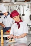 Female Chef Garnishing Dish In Kitchen. Female chef garnishing dish with male colleague in background Royalty Free Stock Photos