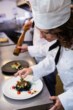 Female chef garnishing meal on counter. In commercial kitchen Royalty Free Stock Images