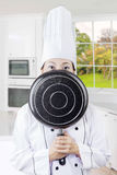 Female chef hiding her face in kitchen Stock Photography