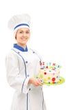 Female chef holding a birthday cake. Isolated on white background royalty free stock photos