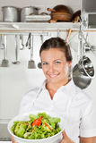 Female Chef Holding Bowl Of Salad. Portrait of female chef holding bowl of salad in restaurant kitchen Royalty Free Stock Photos
