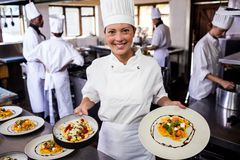 Female chef holding plate of prepared pasta in kitchen. At hotel stock photography