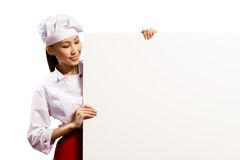 Female chef holding a poster for text Stock Photos