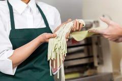 Female Chef Holding Spaghetti Pasta At Kitchen Stock Photo