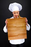 Female chef holding a wooden boards Royalty Free Stock Photography