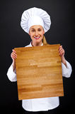 Female chef holding a wooden boards Royalty Free Stock Photo