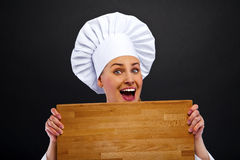 Female chef holding a wooden boards Royalty Free Stock Photos