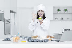 Female chef holds cupcake in kitchen Stock Photos