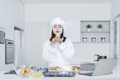 Female chef holds a cupcake in the kitchen Stock Photography