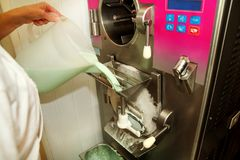 Female chef at ice cream factory is pouring mixed basic ingredients, milk, mixture of mint flavors in maker machine. royalty free stock images