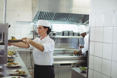 Female chef keeping appetizer plate ready on the order station Royalty Free Stock Images