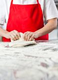 Female Chef Kneading Dough At Messy Counter Royalty Free Stock Photos