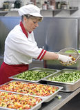 Female chef making salad. A female cook working in a restaurant kitchen, making vegetable salad Royalty Free Stock Photo