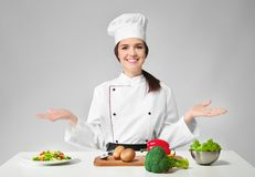 Female chef near table with products. Against grey background stock image