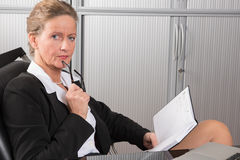 Female chef in the office looking into calendar Royalty Free Stock Photo